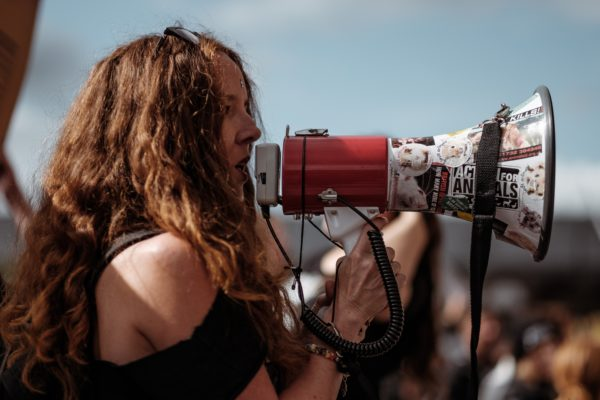 Woman speaking through megaphone at rally, spoken word poetry workshop