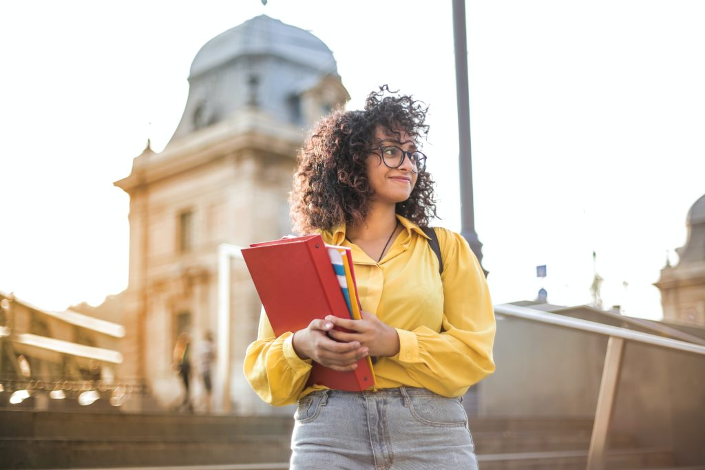 Female student holding books on campus