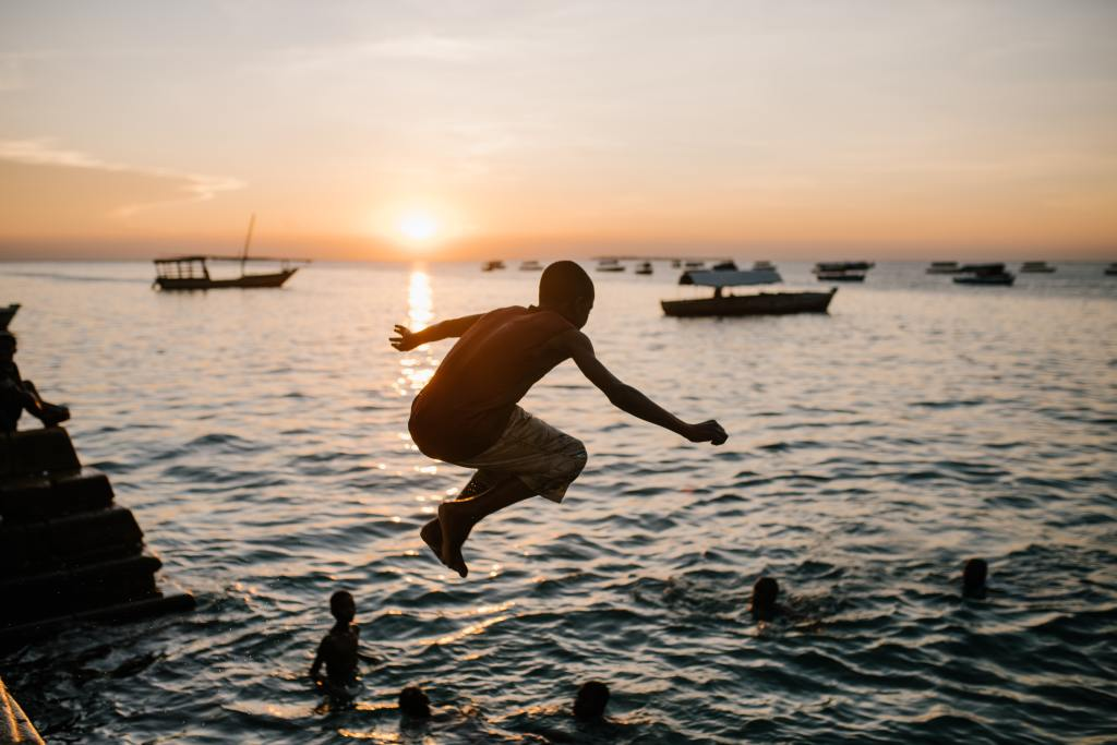 Teen jumping in the water at sunset, College Admissions Essay Tips for Active Verbs